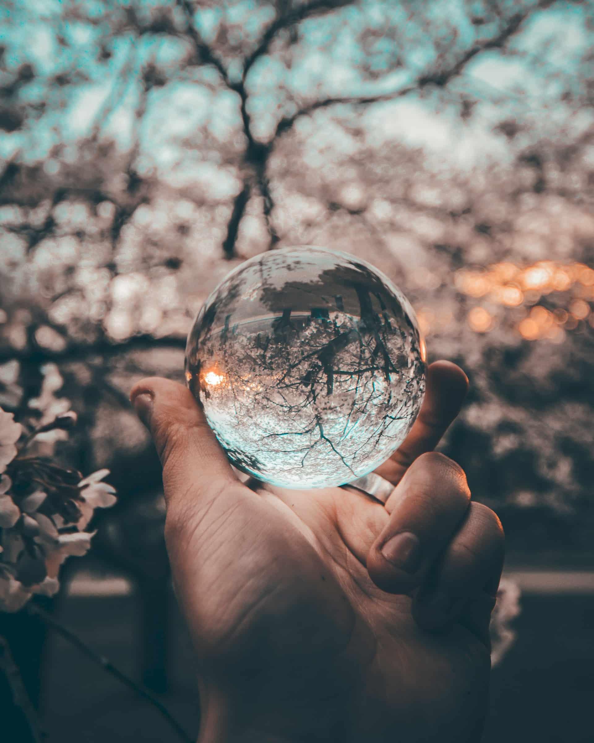 a hand holding a reflective glass ball